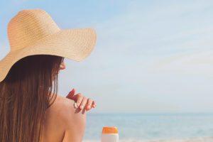 woman putting on sunscreen